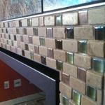 Handmade mosaic glass and stone fireplace border close-up.